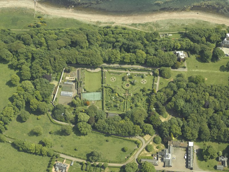 Oblique aerial view centred on the walled garden and orangery with the stables and cottage adjacent, taken from the WNW.