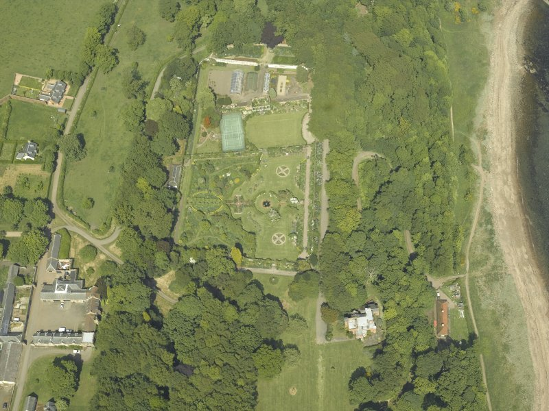Oblique aerial view centred on the walled garden and orangery with the stables and cottages adjacent, taken from the SSW.