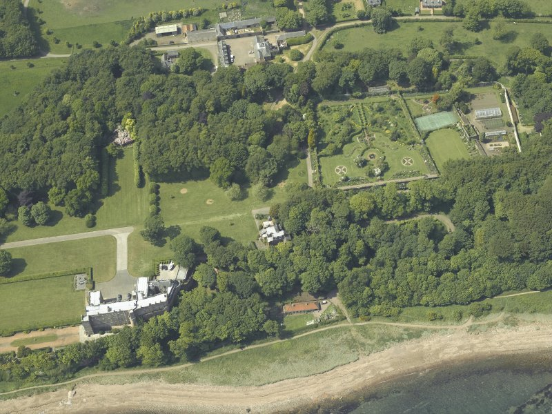 Oblique aerial view centred on the tower-house and walled garden with the stables adjacent, taken from the SE.