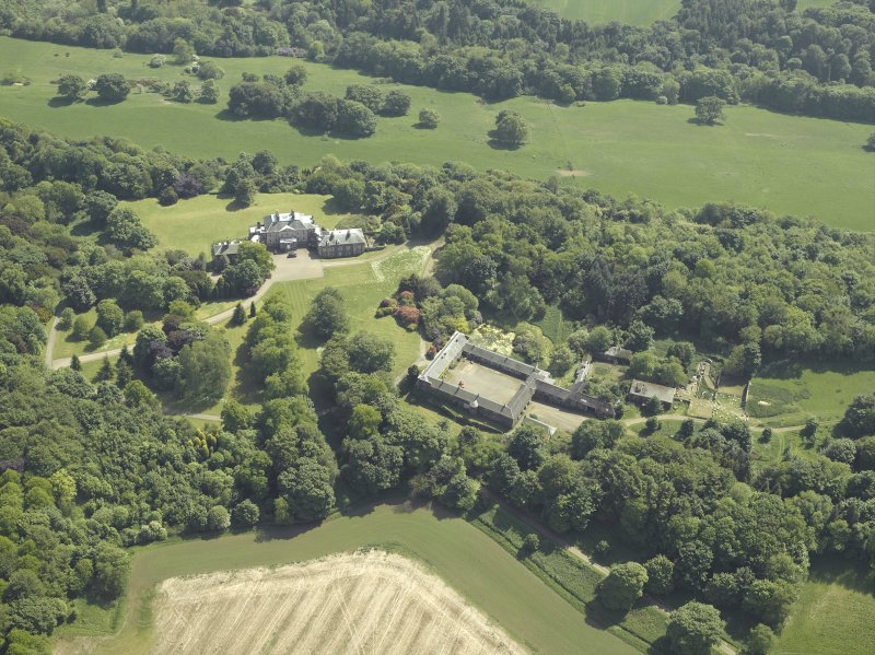 Oblique aerial view centred on the country house and stable block, taken from the NNW.