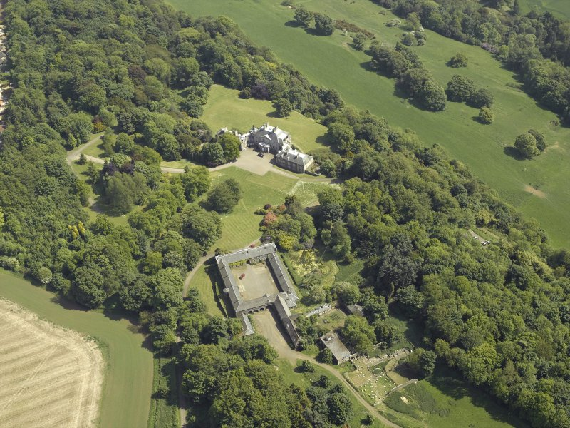 Oblique aerial view centred on the country house and stable block, taken from the NW.