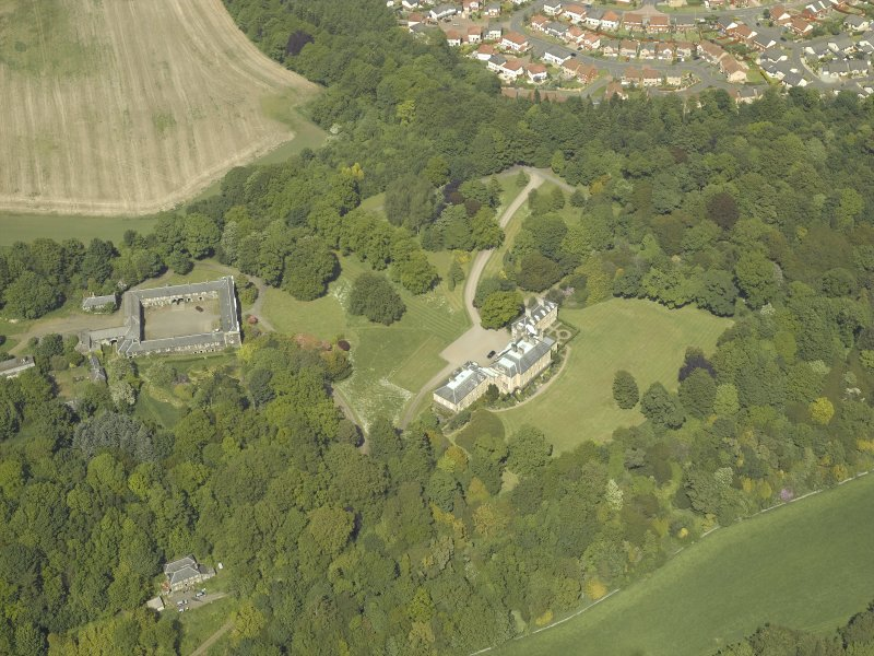 Oblique aerial view centred on the country house and stable block, taken from the SW.