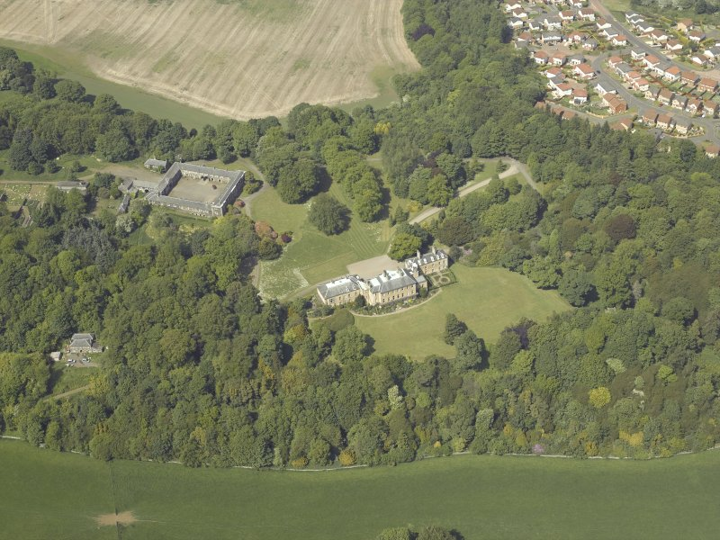 Oblique aerial view centred on the country house and stable block, taken from the S.