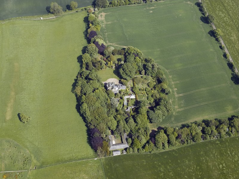 Oblique aerial view centred on the country house, conservatory, dovecot and farmsteading, taken from the WSW.