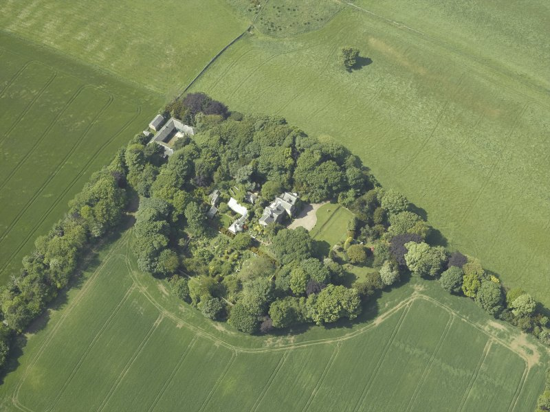 Oblique aerial view centred on the country house, conservatory, dovecot and farmsteading, taken from the ESE.