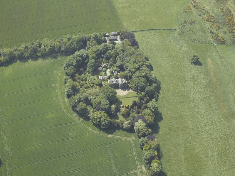 Oblique aerial view centred on the country house, conservatory, dovecot and farmsteading, taken from the E.