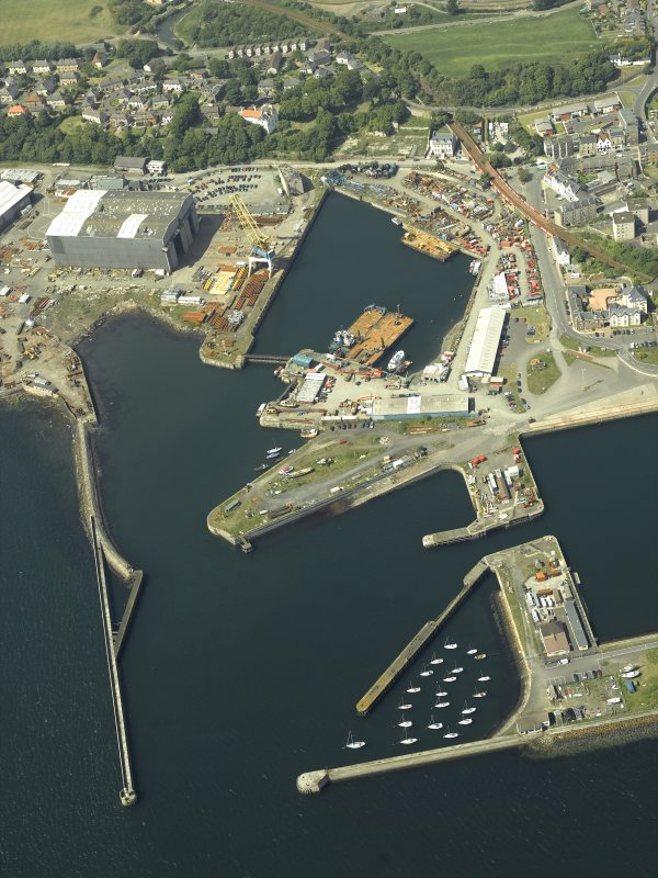 Oblique aerial view of the harbour centred on the outer harbour, breakwaters, dock and engine house, taken from the SSE.
