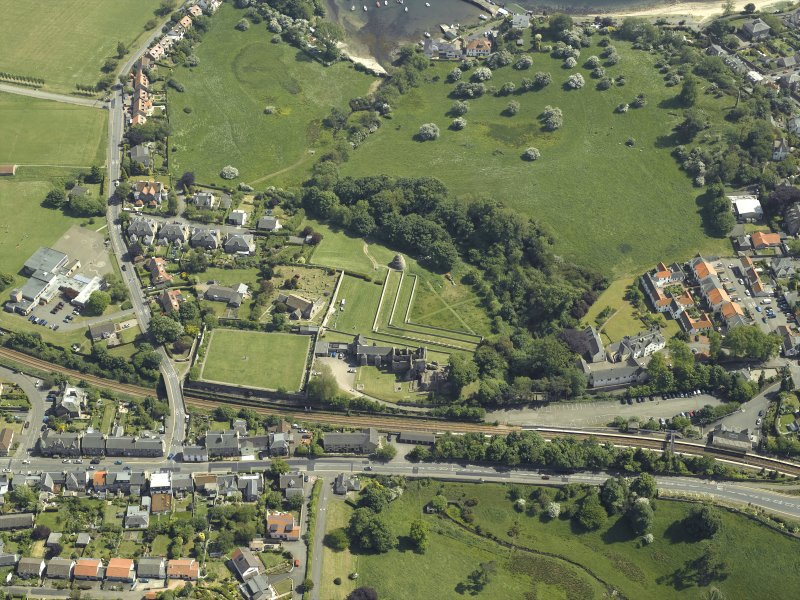 Oblique aerial view centred on the remains of the castle, dovecot and walled garden and the church and burial-ground, taken from the NW.