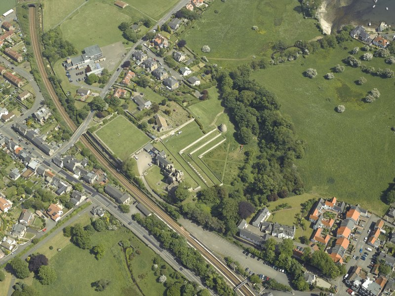 Oblique aerial view centred on the remains of the castle, dovecot and walled garden and the church and burial-ground, taken from the W.