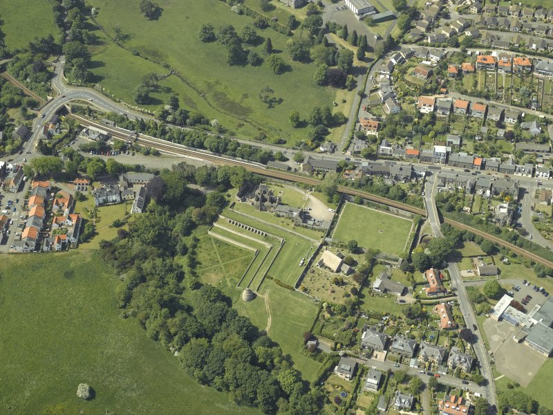 Oblique aerial view centred on the remains of the castle, dovecot and walled garden and the church and burial-ground, taken from the SE.