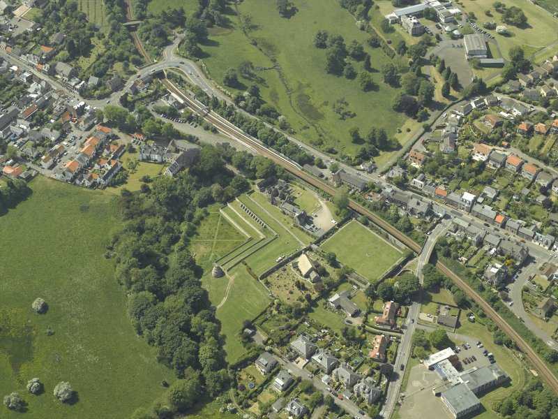 Oblique aerial view centred on the remains of the castle, dovecot and walled garden and the church and burial-ground, taken from the ESE.