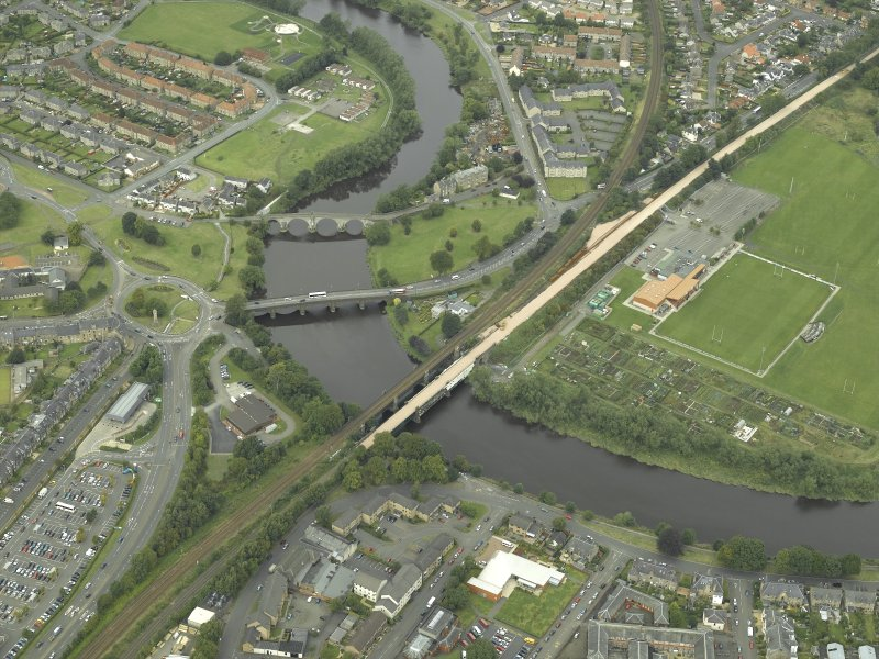 Oblique aerial view of North Stirling showing the railway junction of Stirling to Alloa railway with main Stirling to Perth line. Also visible are the other bridges across the Forth from SE.
