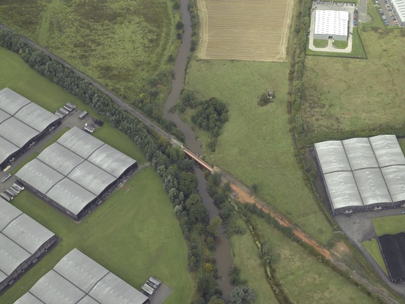 Oblique aerial view.  Railway Bridge over River Devon and part of Cambus Distillery bonded warehouses near Cambus from SE.