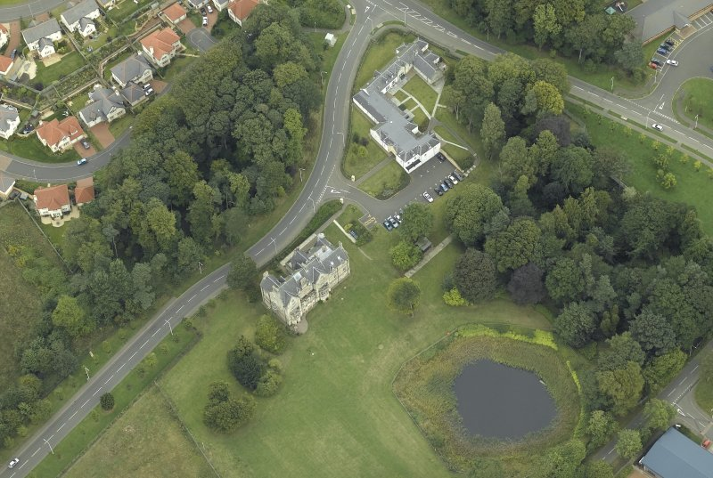 Oblique aerial view centred on the tower-house, farmsteading, stables and garden, taken from the SW.