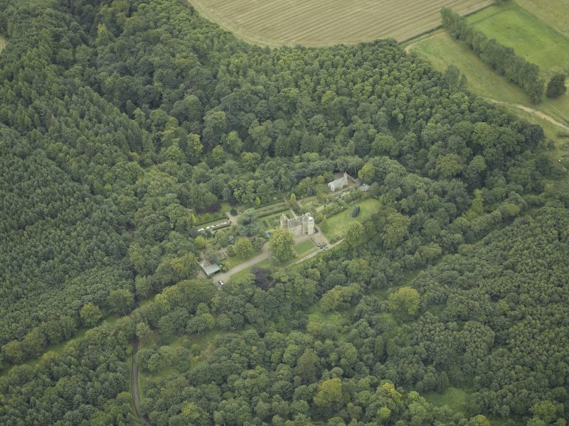 Oblique aerial view centred on the castle, garden and chapel, taken from the NE.