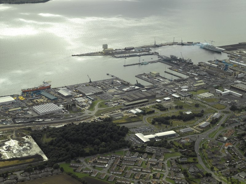 General oblique aerial view centred on the naval dockyard with the remains of the tower-house in the foreground, taken from the NE.