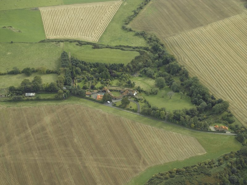 Oblique aerial view centred on the country house, cottage and walled garden, taken from the N.