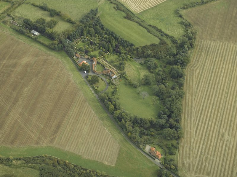 Oblique aerial view centred on the country house, cottage and walled garden, taken from the NW.