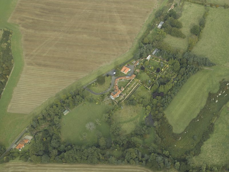 Oblique aerial view centred on the country house, cottage and walled garden, taken from the SW.