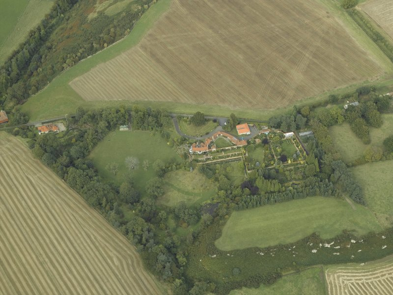 Oblique aerial view centred on the country house, cottage and walled garden, taken from the SSW.