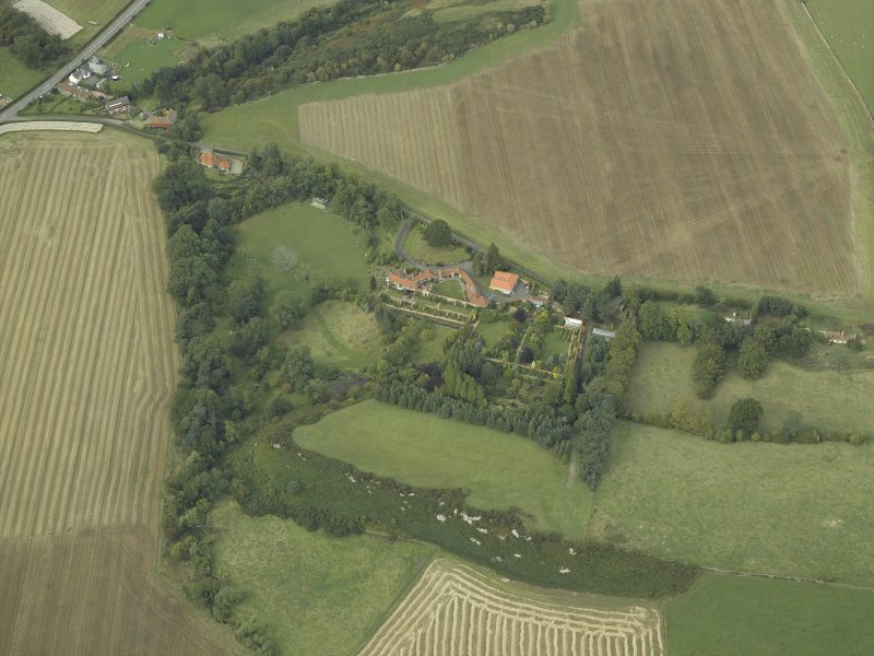 Oblique aerial view centred on the country house, cottage and walled garden, taken from the SSE.