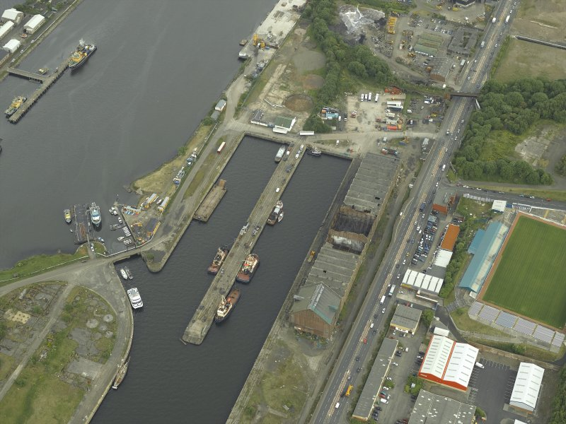 Oblique aerial view centred on the burnt out sugar warehouse and the docks, taken from the WNW.