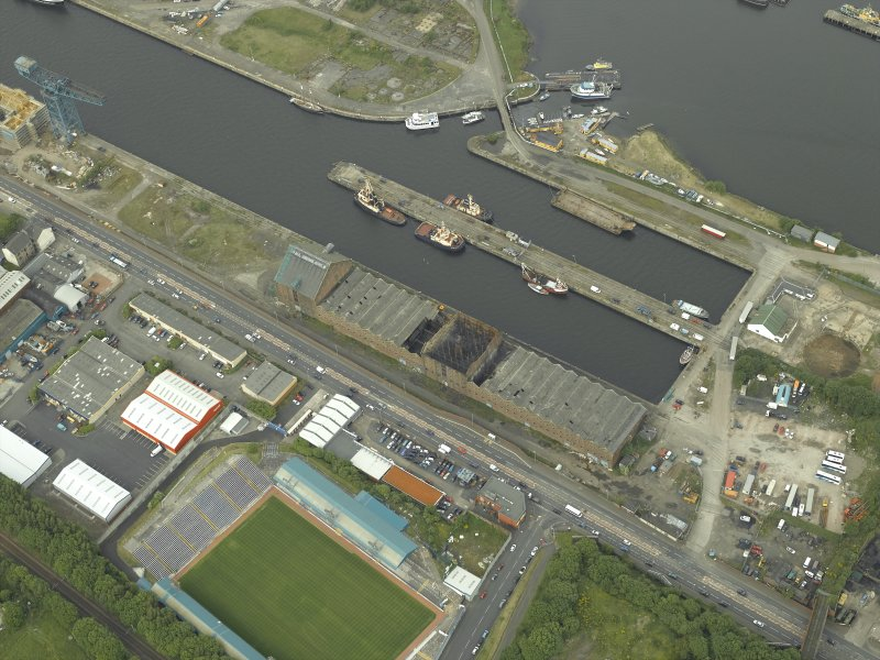Oblique aerial view centred on the burnt out sugar warehouse and the docks, taken from the S.