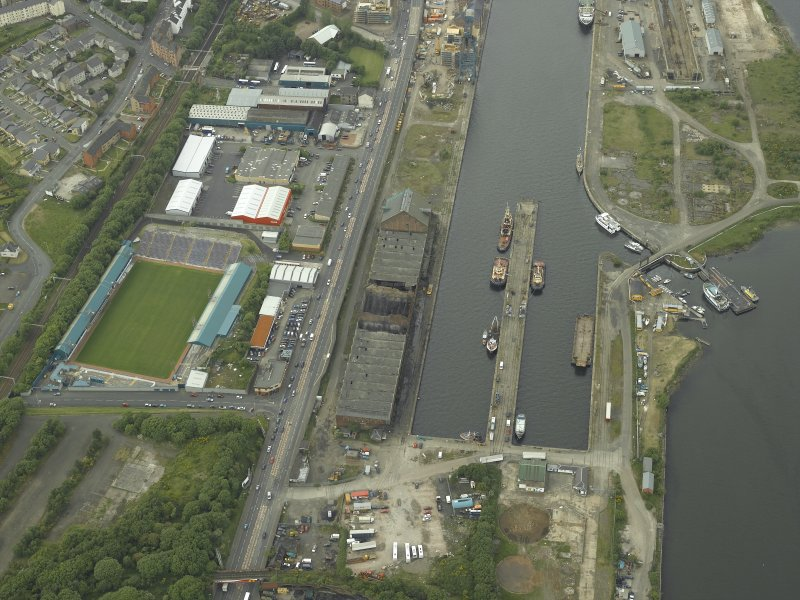 Oblique aerial view centred on the burnt out sugar warehouse and the docks, taken from the ESE.