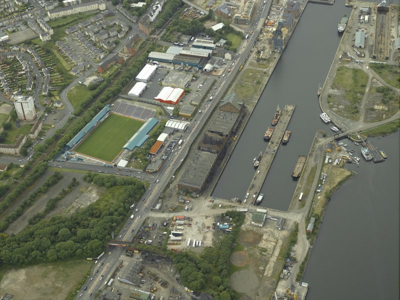 Oblique aerial view centred on the burnt out sugar warehouse and the docks, taken from the E.
