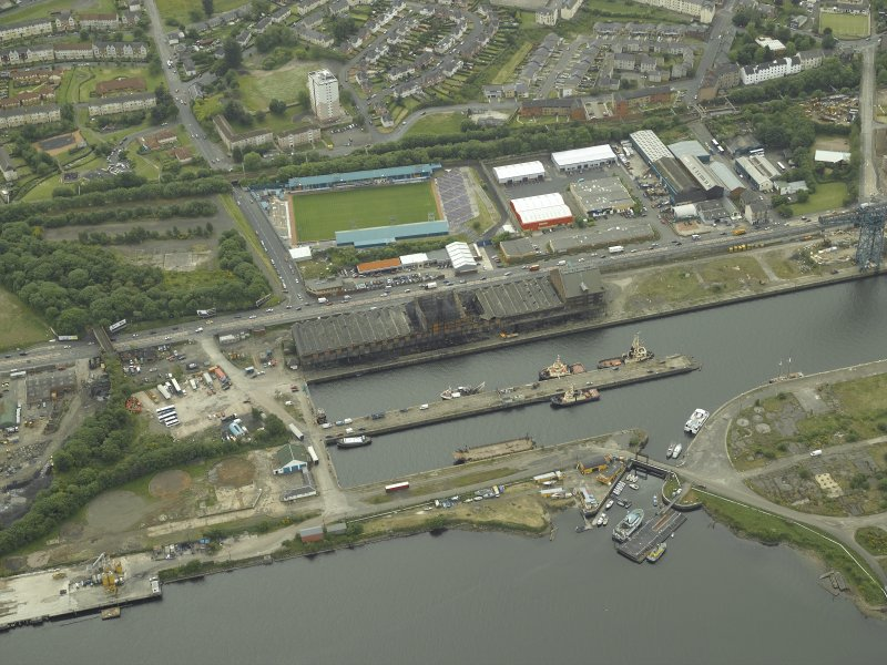 Oblique aerial view centred on the burnt out sugar warehouse and the docks, taken from the NE.