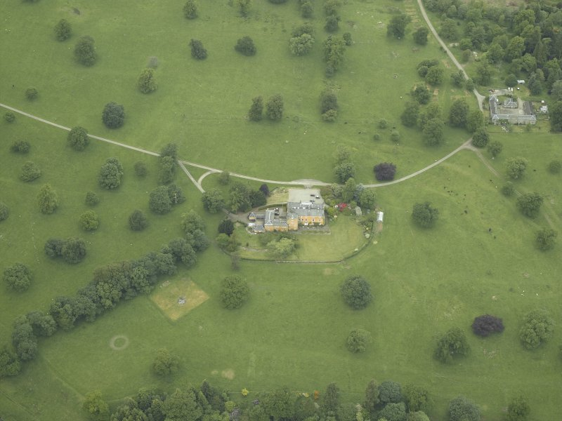 Oblique aerial view centred on the country house, stable block and walled garden, taken from the SE.