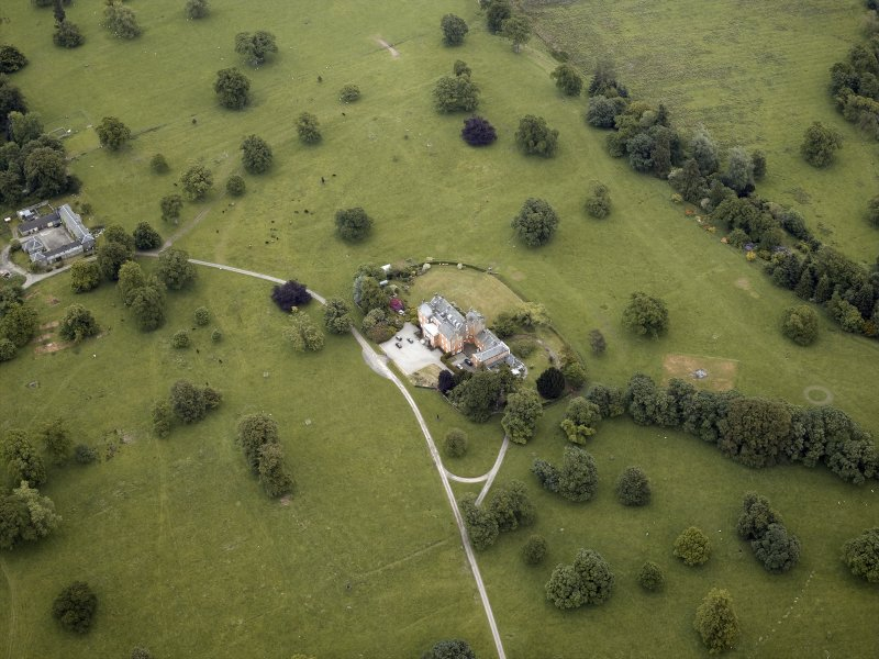 Oblique aerial view centred on the country house, stable block and walled garden, taken from the W.