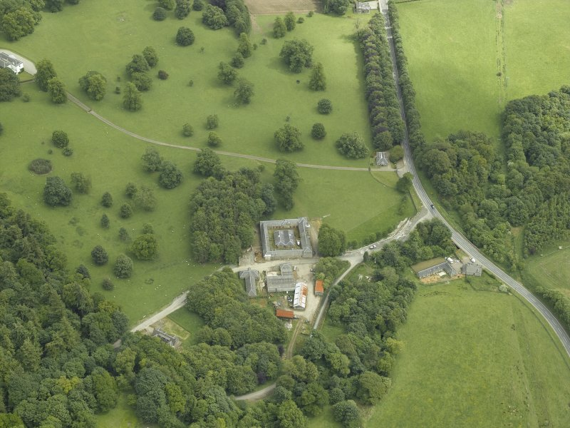 Oblique aerial view centred on the stable block, gate-lodge and road bridge, taken from the WNW.
