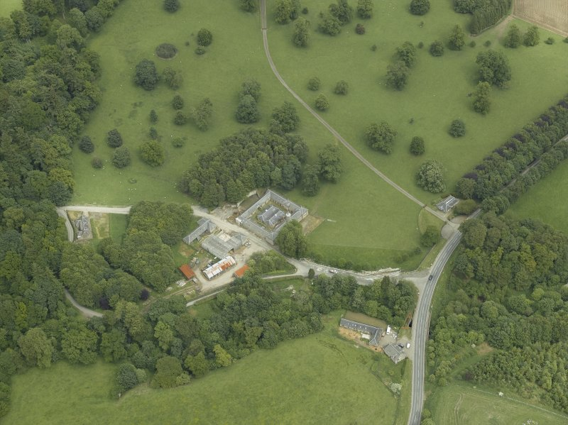 Oblique aerial view centred on the stable block, gate-lodge and road bridge, taken from the WSW.