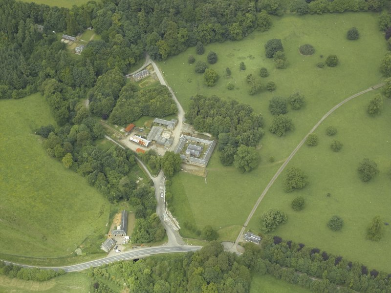 Oblique aerial view centred on the stable block, gate-lodge and road bridge, taken from the S.