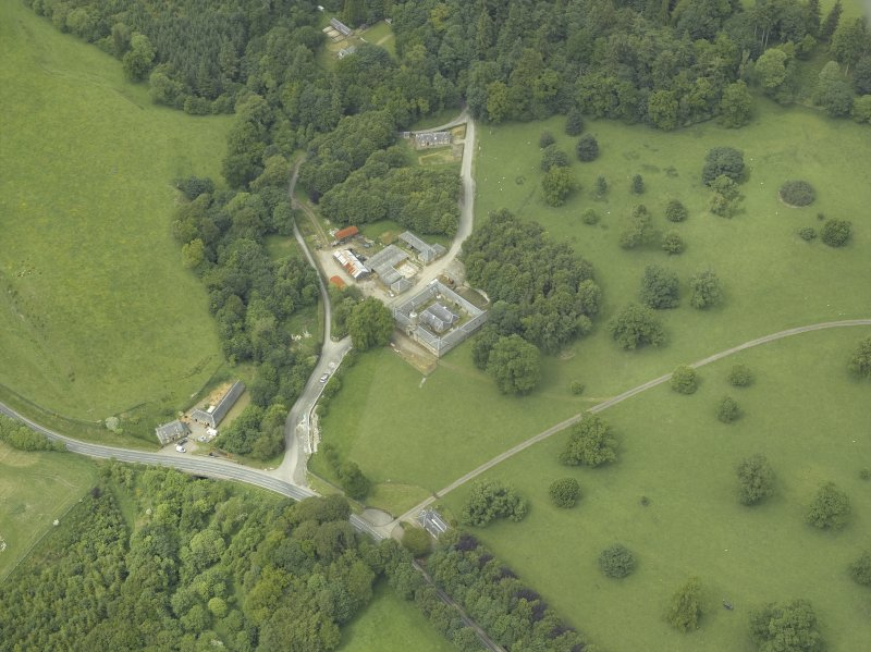 Oblique aerial view centred on the stable block, gate-lodge and road bridge, taken from the SE.