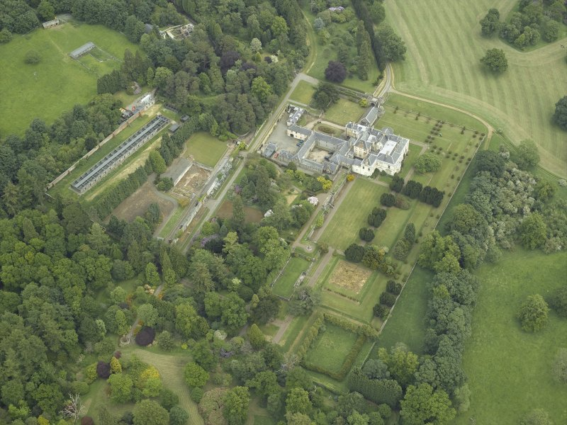 Oblique aerial view centred on the country house, walled garden, gardens and terraces, taken from the WSW.