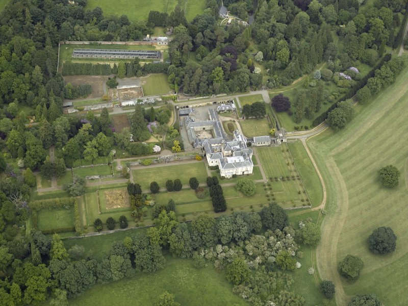 Oblique aerial view centred on the country house, walled garden, gardens and terraces, taken from the SSW.