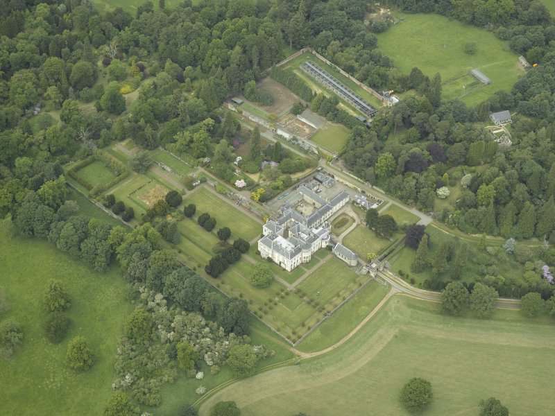 Oblique aerial view centred on the country house, walled garden, gardens and terraces, taken from the SE.