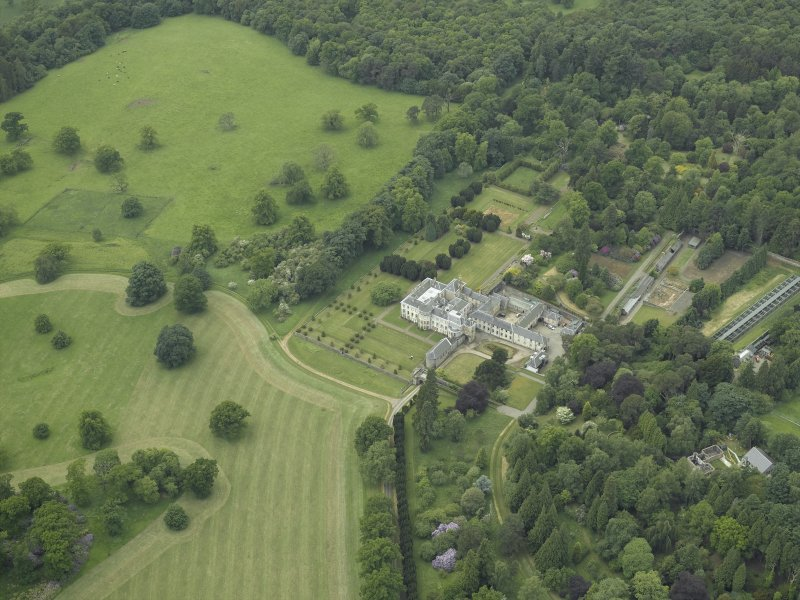 General oblique aerial view centred on the country house, walled garden, gardens and terraces, taken from the E.