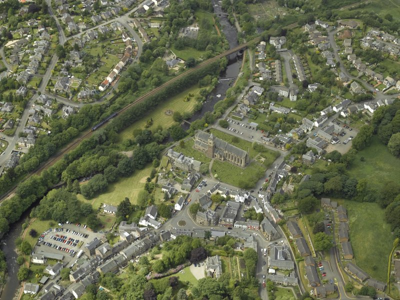 Oblique aerial view of Dunblane centred on the cathedral, chapel, burial-ground and hall with the railway viaduct adjacent, taken from the ESE.
