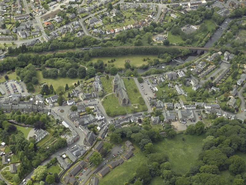 Oblique aerial view of the town centred on the cathedral, chapel, burial-ground and hall with the railway viaduct adjacent, taken from the E.