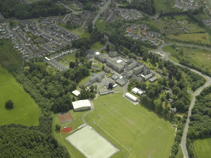Oblique aerial view centred on the school, church, hospital and house, taken from the NE.