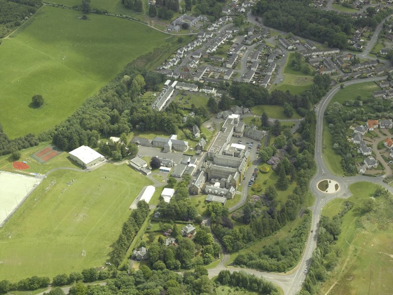 Oblique aerial view centred on the school, church, hospital and house, taken from the NW.