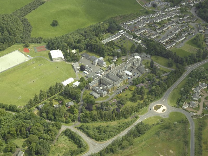 Oblique aerial view centred on the school, church, hospital and house, taken from the WNW.