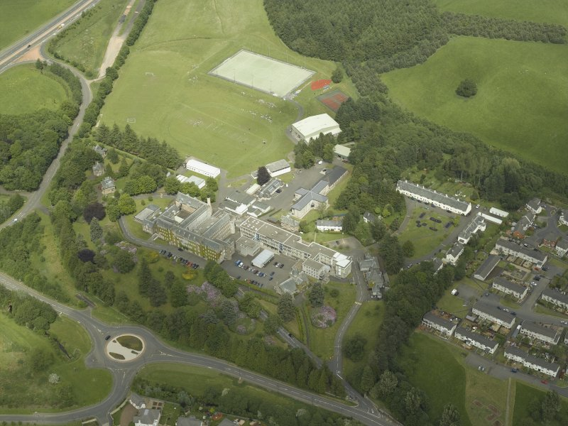 Oblique aerial view centred on the school, church, hospital and house, taken from the SW.