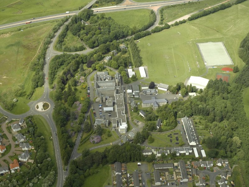 Oblique aerial view centred on the school, church, hospital and house, taken from the SSE.