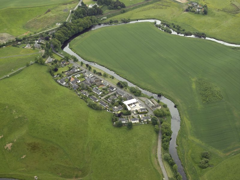 Oblique aerial view of the village centred on the woollen mill, taken from the N.