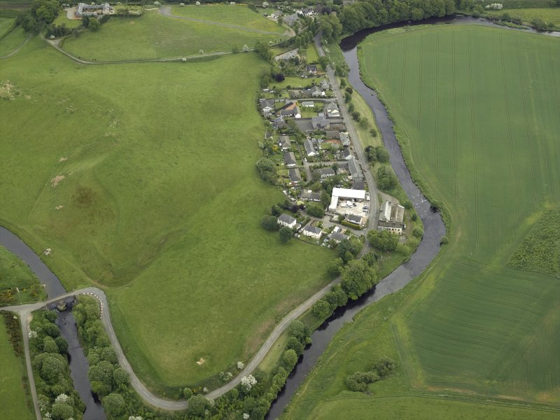 Oblique aerial view of the village centred on the woollen mill, taken from the NW.