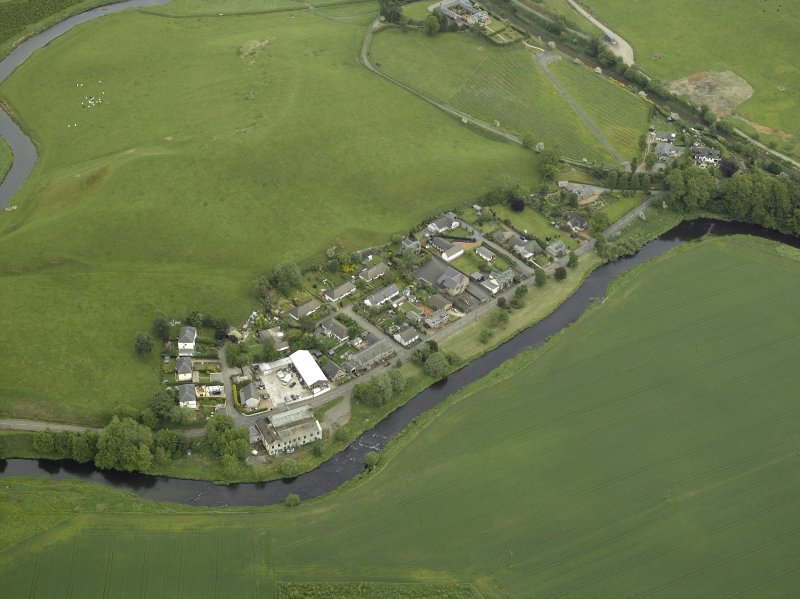 Oblique aerial view of the village centred on the woollen mill, taken from the W.